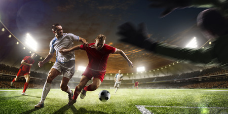 competition success: Soccer players in action on the sunset stadium background panorama Stock Photo