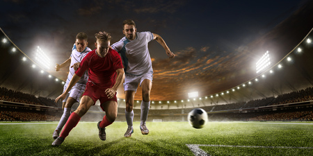 soccer ball on grass: Soccer players in action on the sunset stadium background panorama Stock Photo