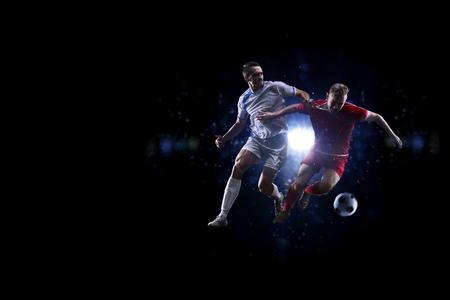 accion: Jugadores de fútbol en acción sobre fondo negro Foto de archivo