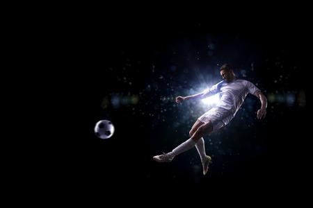 黒の背景の上に空気のサッカー選手 写真素材 - 50612730