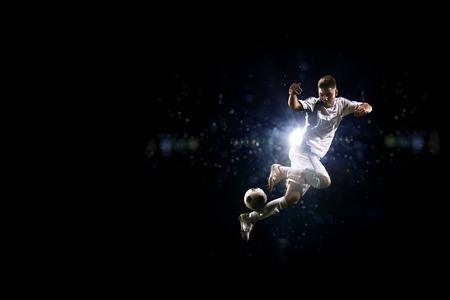 Voetballer in de lucht over zwarte achtergrond
