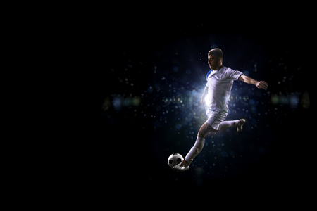 Soccer player in the air over black background Stok Fotoğraf