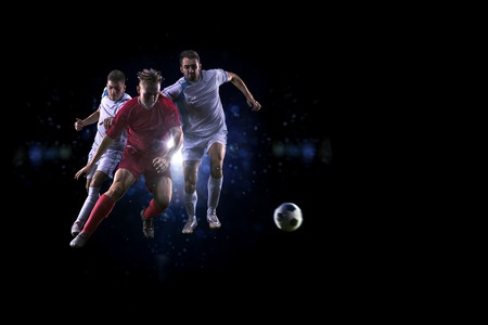 action shot: Soccer players in action over black background Stock Photo