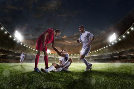 Jugadores de fútbol en acción en el estadio de la puesta de sol de fondo panorama