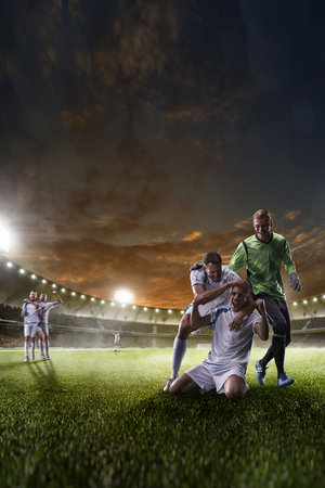 win win: Soccer players in action on the sunset stadium background panorama Stock Photo