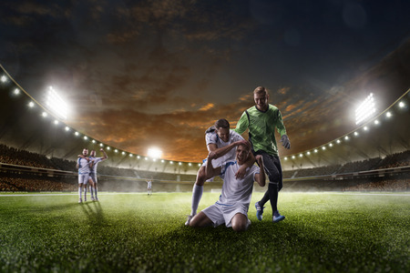 adult foot: Soccer players in action on the sunset stadium background panorama Stock Photo