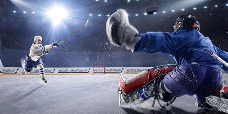 jugador de hockey dispara el disco y los ataques Foto de archivo