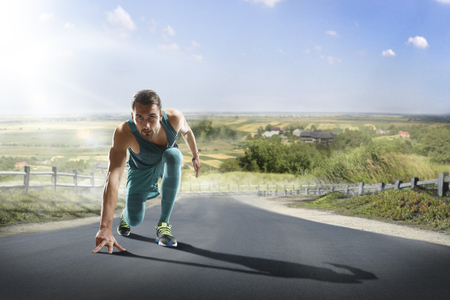 male athlete: Running athlete man. Male runner sprinting during outdoors training for marathon run. Athletic fit young sport fitness model in his twenties in full body length on road outside in nature.