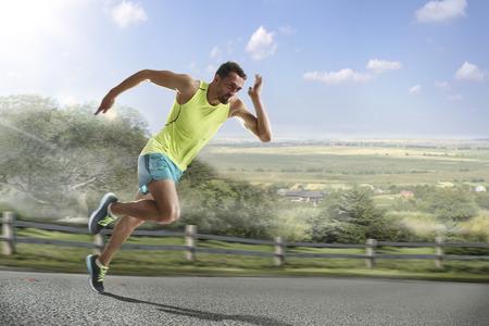 Laufender Athlet Mann. Mann Läufer sprintet während draußen für Marathonlauf trainieren. Sportlich fit junge Sportart Fitness-Modell in seinen zwanziger Jahren in voller Körperlänge auf der Straße draußen in der Natur. Standard-Bild