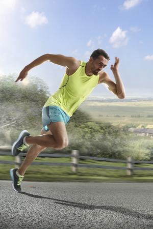Uruchamianie sportowiec człowieka. Mężczyzna sprint biegacz podczas treningu na świeżym powietrzu na metę maratonu. Athletic Fit młoda sportu fitness model w jego dwudziestych w pełnej długości ciała na drodze na zewnątrz w przyrodzie.
