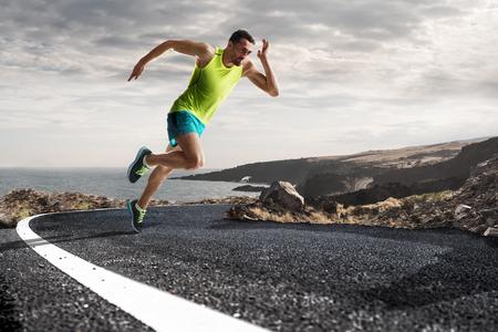 Courir athlète homme. Homme sprint coureur lors de l'extérieur la formation pour le marathon run. modèle Athletic ajustement jeune sportif de fitness dans la vingtaine en pleine longueur du corps sur la route à l'extérieur dans la nature.