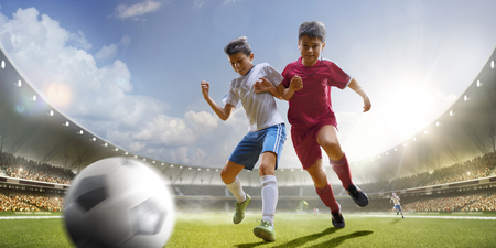 elementary age boys: Childrens are playing soccer on grand arena in sunlights Stock Photo