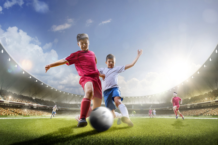 Childrens are playing soccer on grand arena in sunlights Standard-Bild