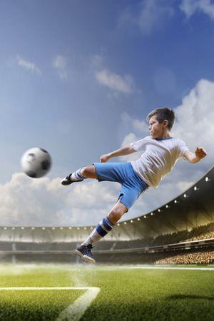 Childrens are playing soccer on grand arena in sunlights Stock Photo