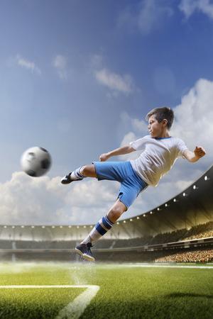 Enfants jouent au football sur grande arène dans sunlights Banque d'images