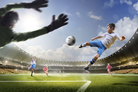 child ball: Childrens are playing soccer on grand arena in sunlights Stock Photo