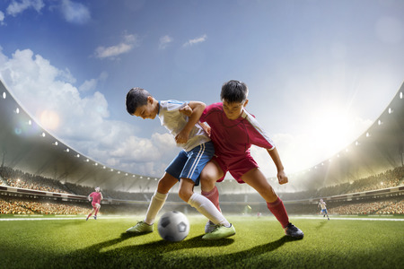 Childrens are playing soccer on grand arena in sunlights Archivio Fotografico