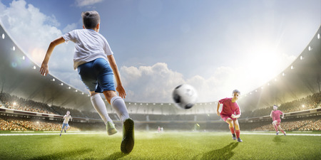 people in action: Childrens are playing soccer on grand arena in sunlights Stock Photo