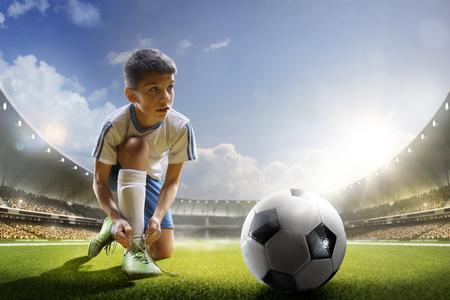 日光のグランド アリーナでサッカーをプレイしている子供 写真素材