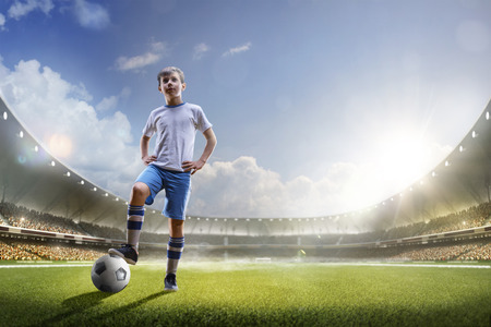 Childrens are playing soccer on grand arena in sunlights Stockfoto
