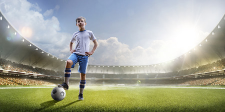 Childrens are playing soccer on grand arena in sunlights Stok Fotoğraf - 57366074