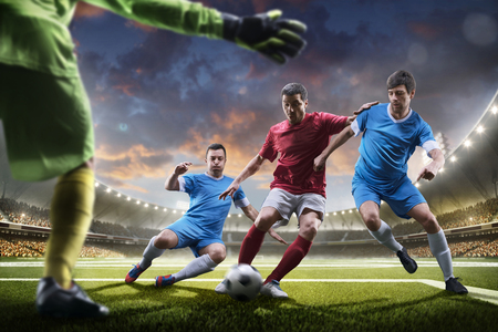 football symbol: Soccer players in action on the sunset stadium background panorama Stock Photo