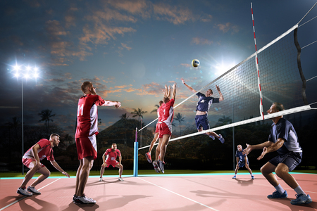 Professional volleyball players in action on the night open air court Imagens