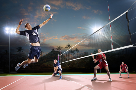 Professional volleyball players in action on the night open air court Stockfoto