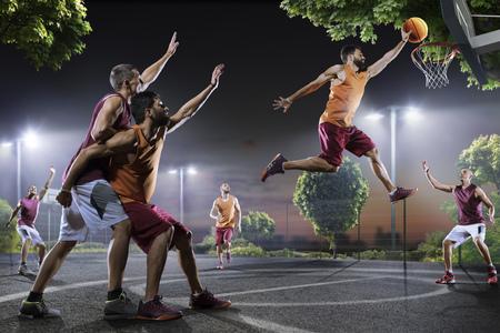 夜のコート上のアクションでストリート ボール選手 写真素材
