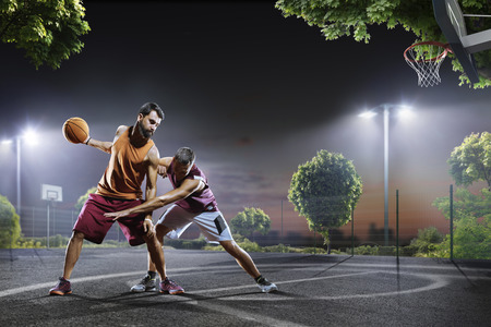 Streetball players in action on night court