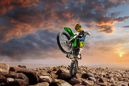 Professional dirt bike rider doing wheely on the top of vulcan