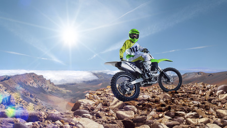 motorsprot: Brave professional dirt bike rider pose on the top of vulcan Stock Photo