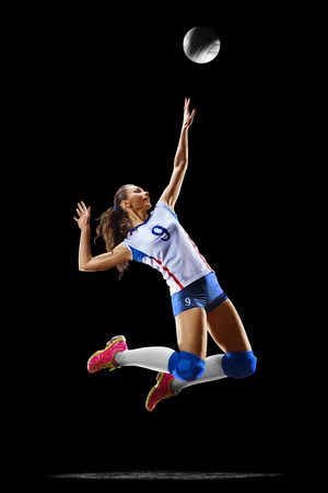 Female professional volleyball player isolated on black