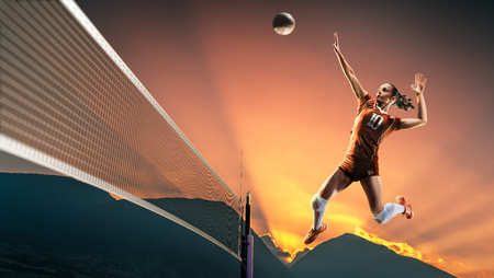 Professional female volleyball player in action at the sunset
