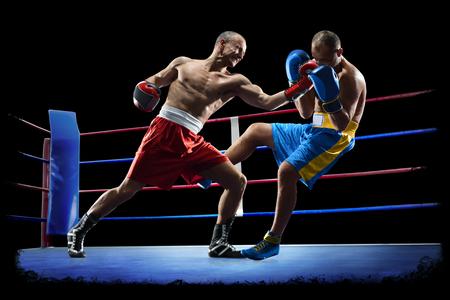 Los boxeadores profesionales están aislados sobre fondo negro oscuro