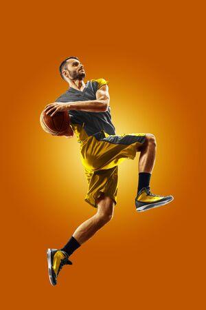 bright professional basketball player on the orange background Banco de Imagens