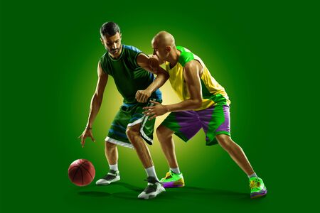 colourful professional basketball players isolated over green background