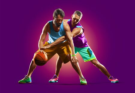 bright colourful professional basketball players isolated over purple background Banco de Imagens