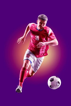 colourful professional soccer player isolated over purple background