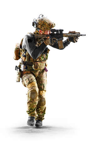 Army soldier in Protective Combat Uniform holding Special Operations Forces Combat Assault Rifle isolated on white background