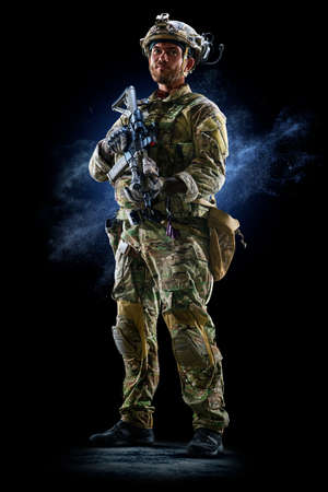 Army soldier in Protective Combat Uniform holding Special Operations Forces Combat Assault Rifle on dark background
