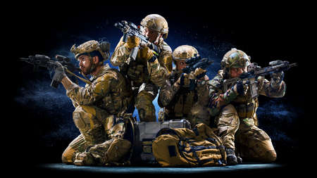 Army soldiers in Protective Combat Uniform holding Special Operations Forces Combat Assault Rifle on dark background
