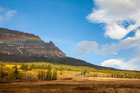 Rainbow on an autumn day in front of a mountain near Saint Mary