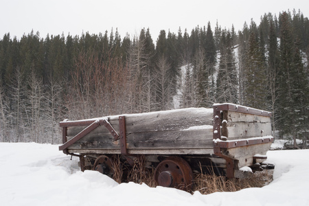 Old abandoned coal car in the winter forest