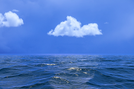 Background of sky with and a single cloud reflected in water or ocean Stock Photo