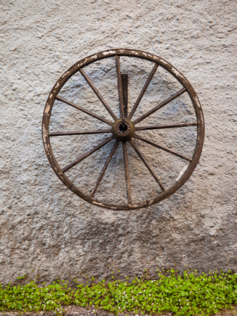 An old wagon wheel displayed on a rustic old wall, Austria
