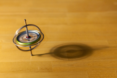 Toy gyroscope spinning and balancing on a wooden table