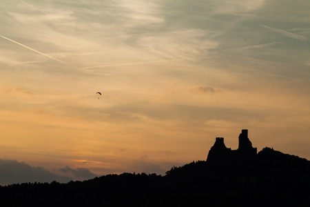 Paraglider flying over Trosky Castle in the Czech Republic, Europe