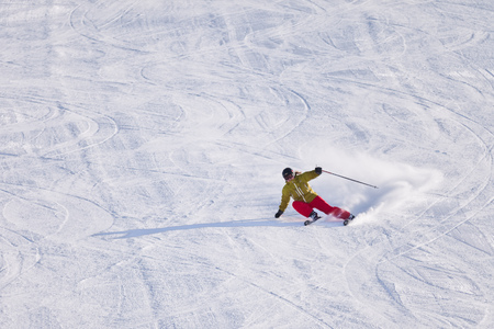 Young woman downhill skiing on an open slope at a ski resort in the Canadian Rocky Mountains, Alberta, Canada