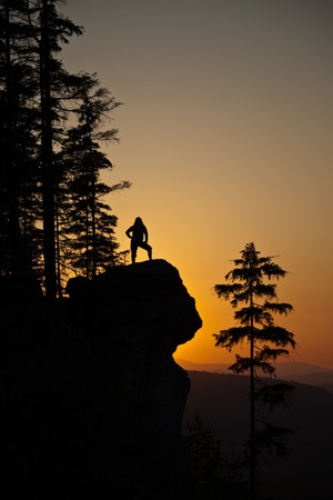 Silhoutte of a young woman posing on a rocky cliff against a colorful sunset, In Czechia, Europe